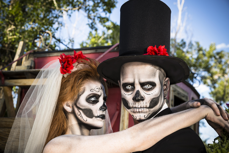 Characters: Skeleton bride wraps arms around groom. Spooky Halloween wedding.