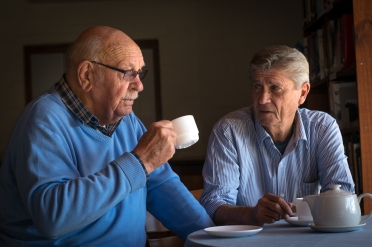 Two senior men consoling one another over a cup of coffee